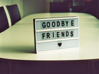 "sign reading ""goodbye friends"" left on a conference room table"