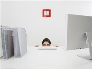 woman hiding behind a desk