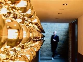 person rounding the corner into a  well-lit hallway covered in gold-tinted lights