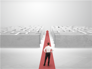 A businessman cutting a path and rolling a red carpet through the heart of the maze - Reducing IT complexity concept