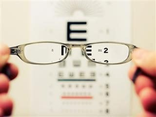 a pair of glasses focusing on a vision chart