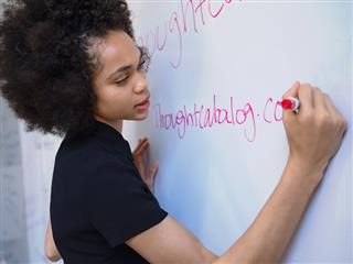 woman writing on a white board