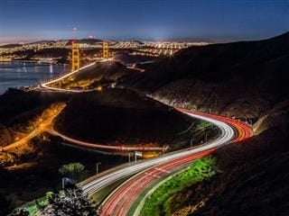 time lapse photography of a highway at night approaching the Golden Gate Bridge