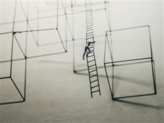 human figure climbing a ladder surrounded by geometrical shapes