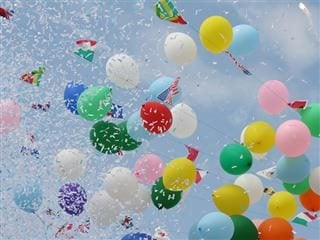 Multi-colored balloons and confetti in a blue sky.