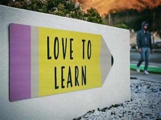 "sign in the shape of a number 2 pencil which states ""Love to Learn"""