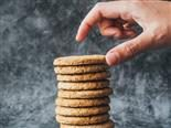 a hand reaching for the  top cookie in  a stack