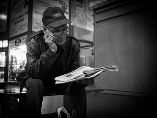 A man sitting down reading a newspaper. Black and white photo.
