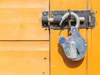 open padlock on an orange colored door
