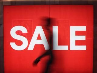 silhouette in front of a sale sign