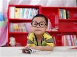 child with glasses reading a book