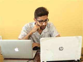 man looking at a PC and a Mac