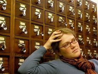 a librarian, in front of a card catalogue