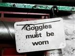 "sign reading ""goggles must be worn"""