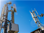 A shot of 5G towers against a blue sky - remote work and 5G concept