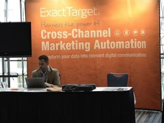 An ExactTarget representative sits in front of a sign about the company's marketing automation product.