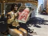 Street view with La Lectora, bronze statue of a woman reading Diario Cordoba or Cordoba Newspaper, monument to the 75th anniversary of the newspaper by Marco Augusto.