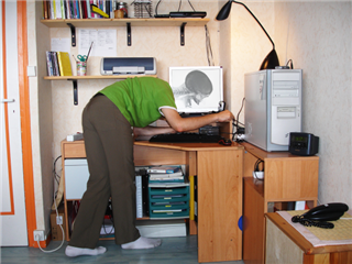 A man working on a a computer in his home office. The means head is behind the monitor and the monitor is displaying a human skull making it seem like he is headless - headless cms concept