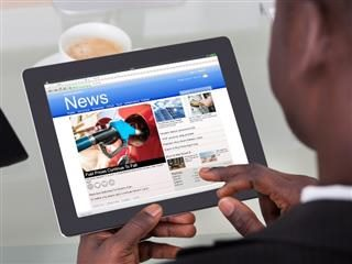 Man reading the news on a tablet.
