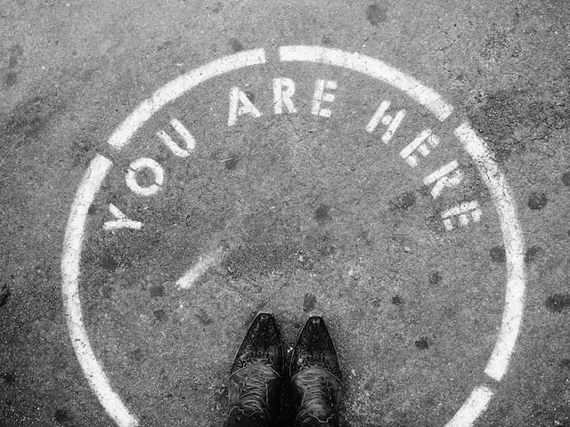 """shoes in a circle on pavement with writing stating """"you are here"""""""