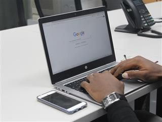 man starting a Google search on a laptop