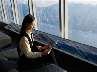 A businesswoman working remotely via her tablet. Sitting at a window - Unified Communications Concept