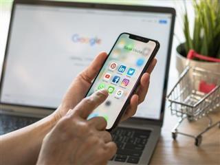 Un utilisateur de médias sociaux assis à son bureau d'ordinateur se connectant à un site de médias sociaux - concept de marketing des médias sociaux