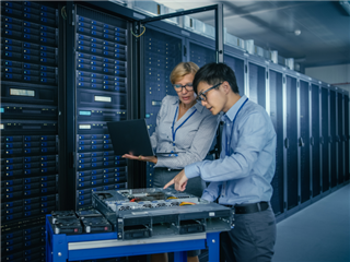 Two IT pros working on a server that powers cloud computing