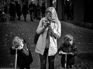 woman with children, using cell phone