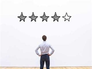 "A man staring at a whiteboard with ""rating"" stars"