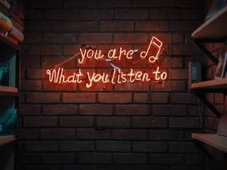 "neon sign reading: ""you are what you listen to"""