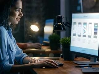 Female Mobile Web Developer Working at Her Desk top PC, Creating a Mobile Wireframe.