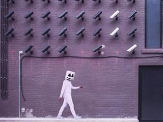figure with mask on walking past a wall of surveillance cameras