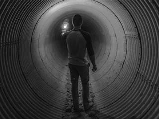 walking through a large pipe with a light ahead