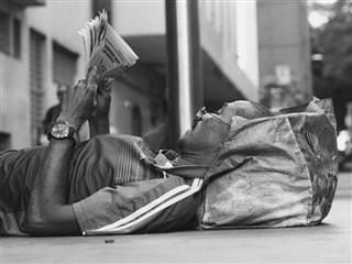 laying on the sidewalk, reading a newspaper
