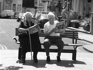 Woman and man sitting on a bench reading a newspaper in a black-and-white photo.