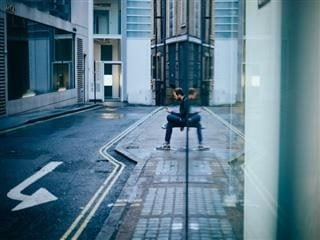 contextual commerce - man on phone with reflection in building