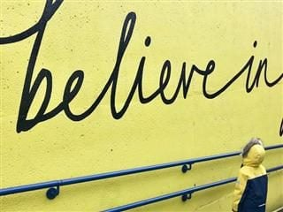 "sign reading ""believe in"" painted on a yellow wall. Child with yellow and black parka on staring up at it"