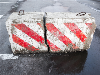 Concrete road block with warning red and white diagonal striped pattern