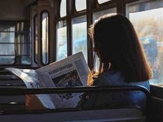 woman reading a newspaper on a bus