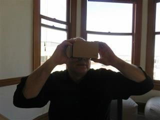 A man holding up a VR headset.
